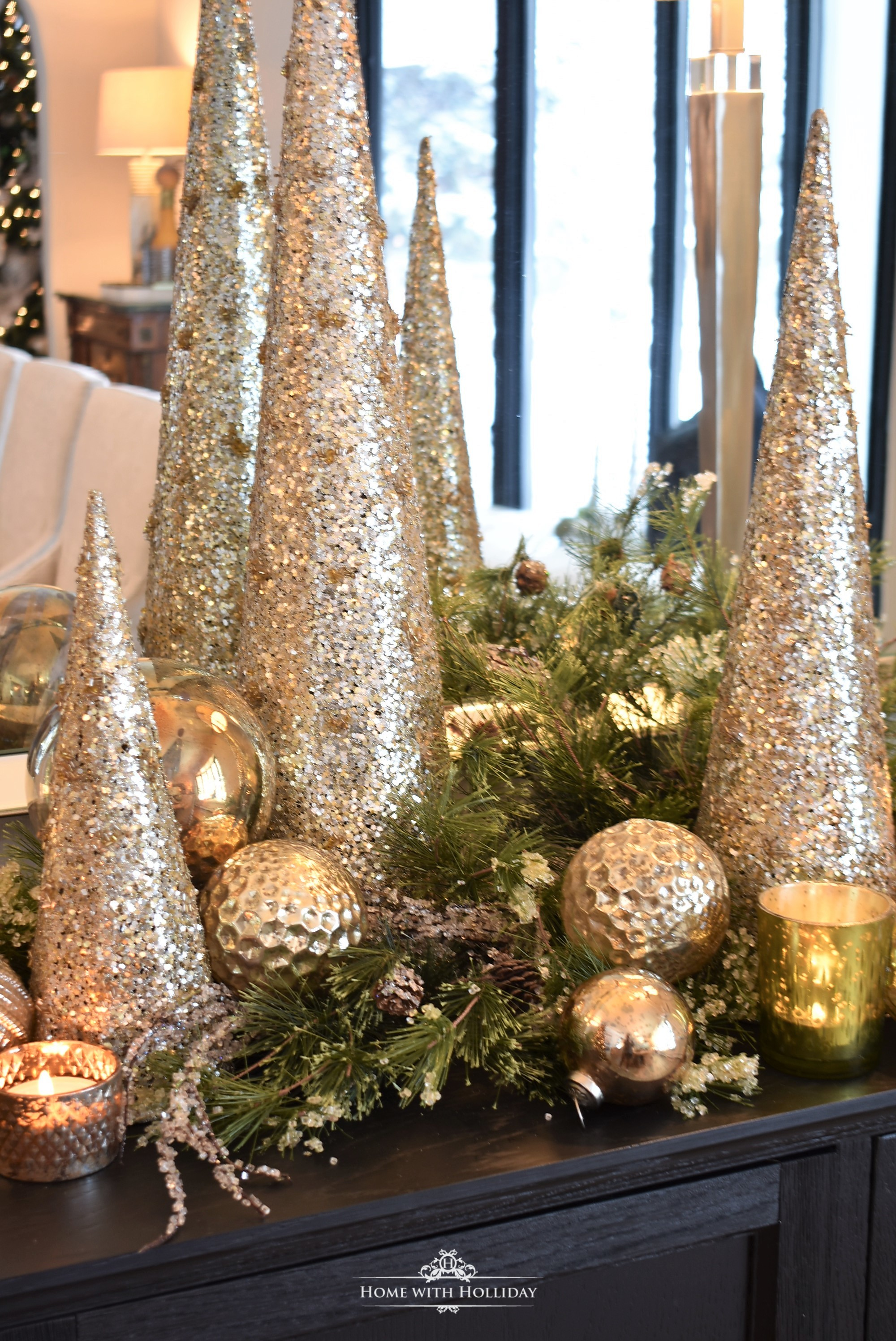 Simple Silver and Gold Glam Christmas Centerpiece with gold cone treed and ornaments on a black buffet