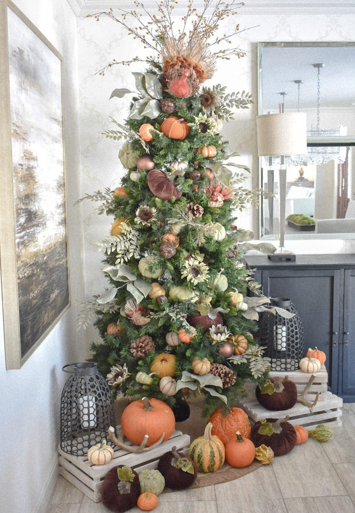 A Christmas Tree decorated for fall with pumpkins and fall decor