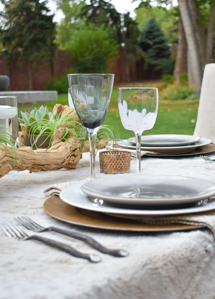 A view of a Neutral Fall Alfresco Dining Tablescape with a throw blanket and succulents