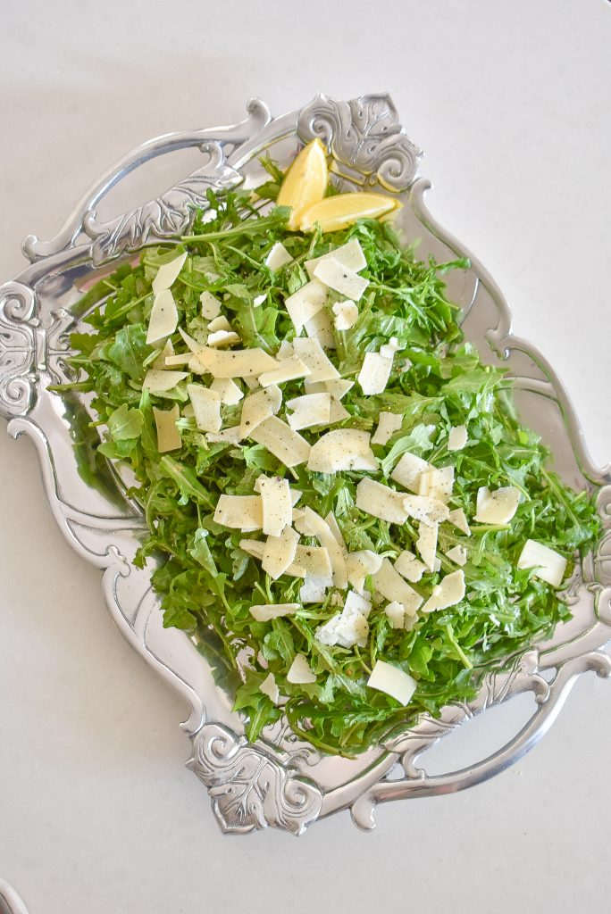 A Simple Arugula Salad with Lemon Vinaigrette Dressing on a serving platter