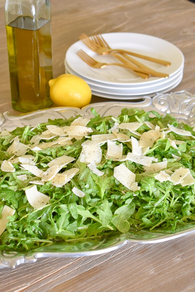 A Simple Arugula Salad with Lemon Vinaigrette Dressing on a Tray