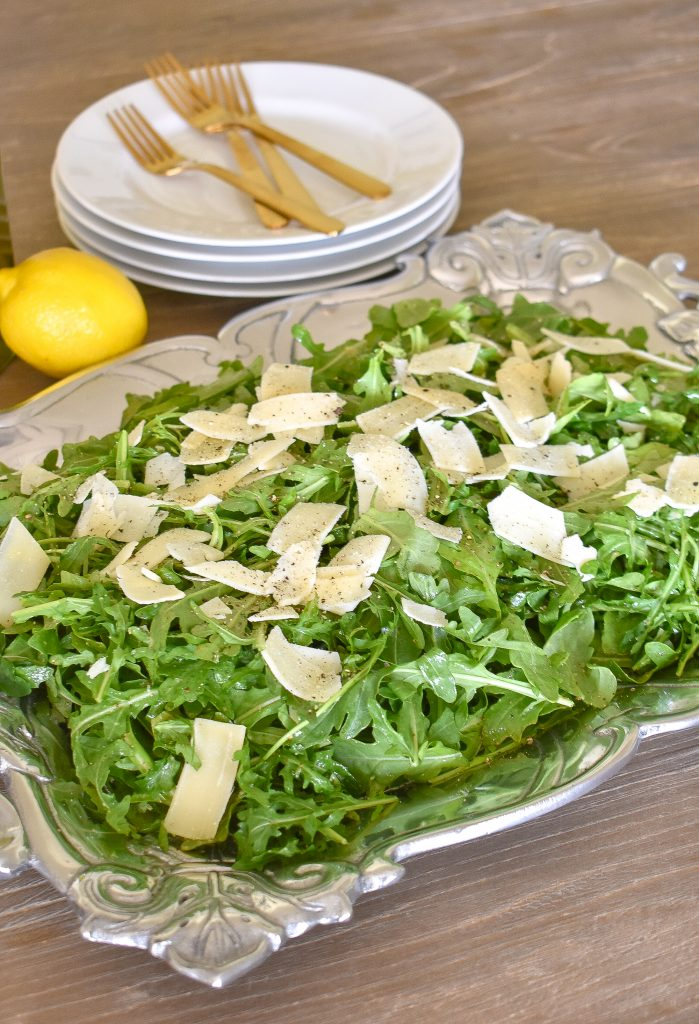 Arugula Salad with Lemon Vinaigrette Dressing on a tray ready to serve
