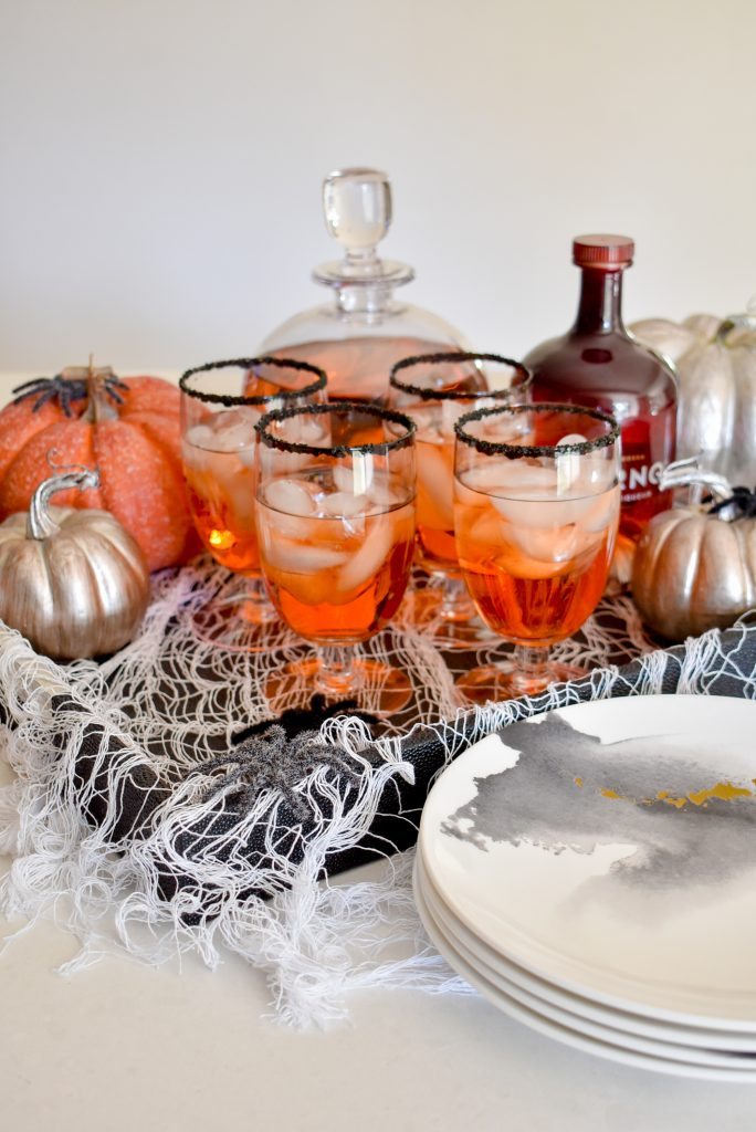 Blood Orange and Vodka Cocktail on a black tray with white spider webbing