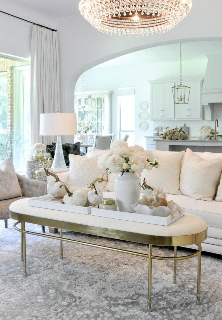 Elegant white and gold fall decor on a white ottoman