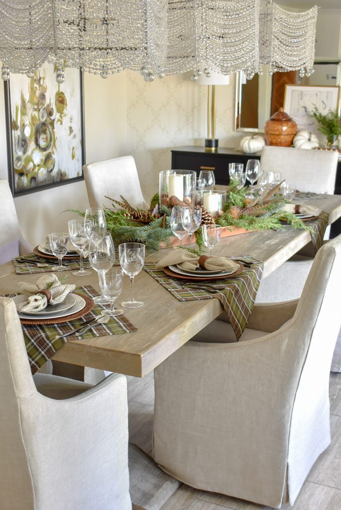 A Casual Evergreen Thanksgiving Table Setting with plaid and pine cones