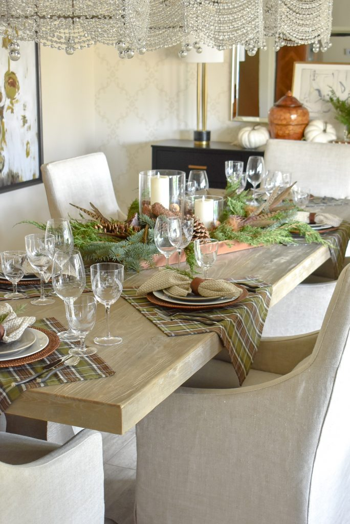 A Simple, Casual Evergreen Thanksgiving Table Setting with plaid and green and brown tones