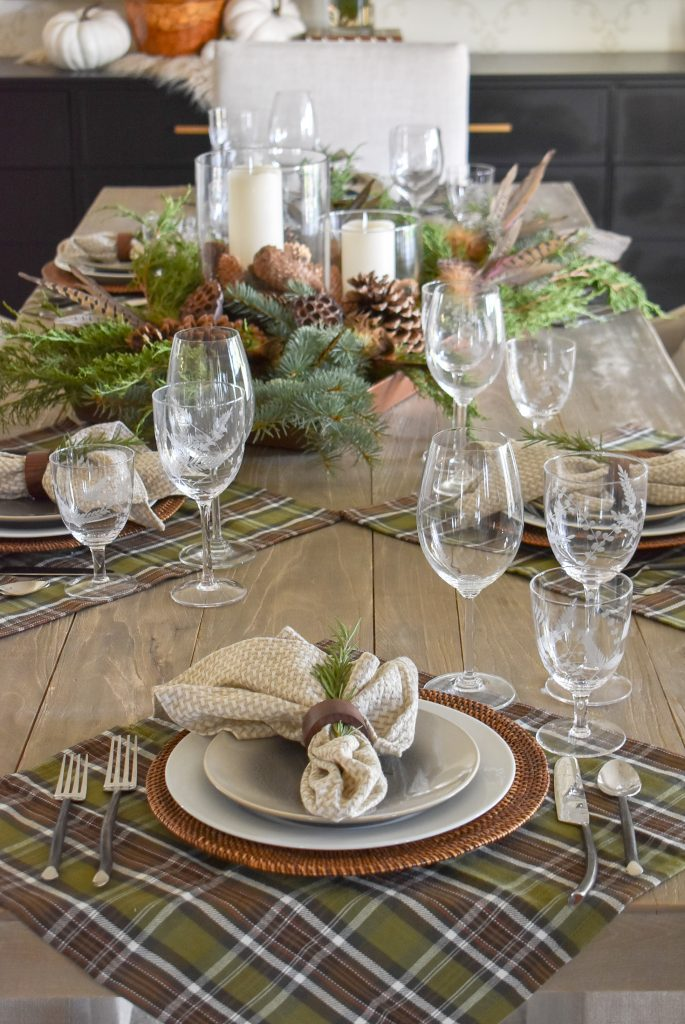 A Casual Evergreen Thanksgiving Table Setting with pine cones and plaid