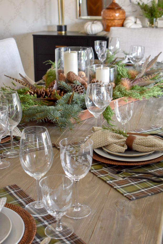 A Simple and Casual Evergreen Thanksgiving Table Setting with plaid and pine cones