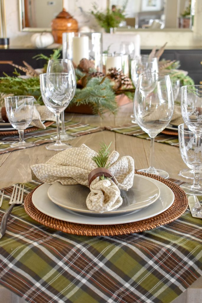 A Simple, Casual Evergreen Thanksgiving Table Setting with plaid napkins