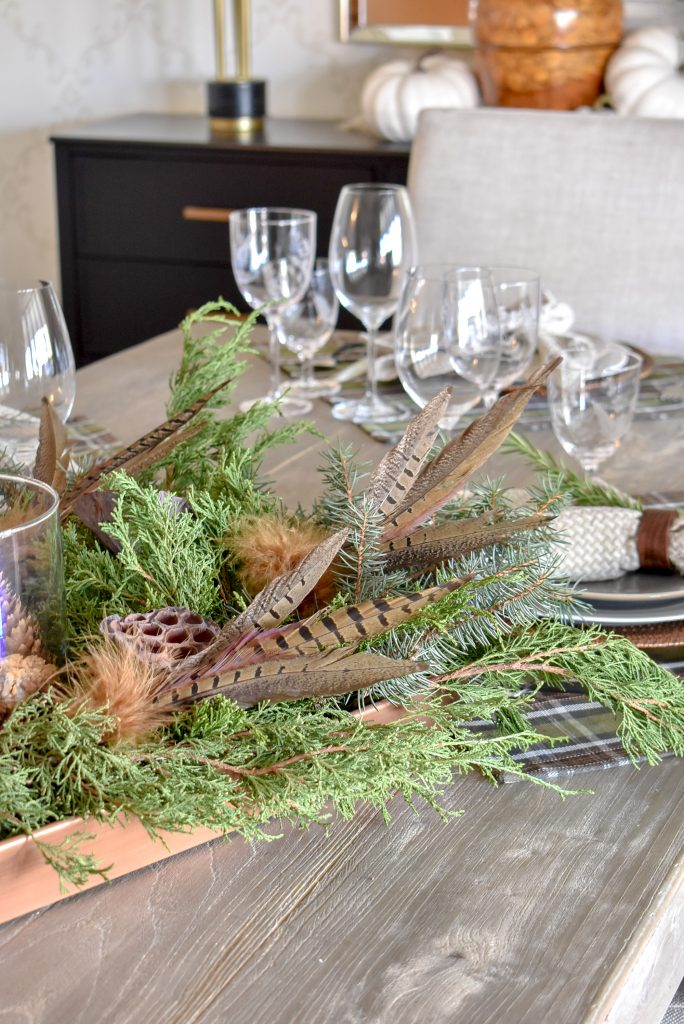 Natural Centerpiece on a A Simple, Casual Evergreen Thanksgiving Table Setting with pine cones and feathers