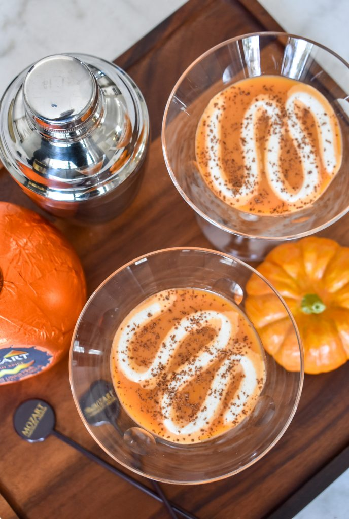 A Creamy Chocolate Pumpkin Spice Martini with whipped cream on a wood tray