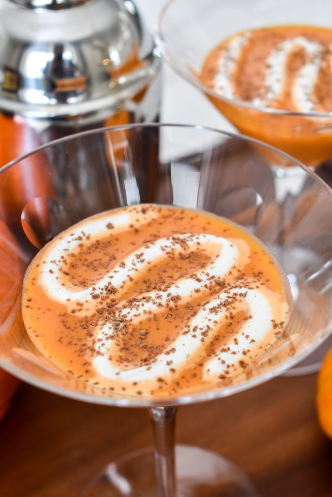 A Creamy Chocolate Pumpkin Spice Martini with whipped cream and chocolate shavings