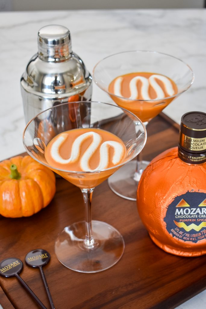 Two Creamy Chocolate Pumpkin Spice Martinis on a tray with whipped cream