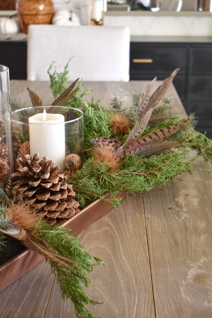 Natural greenery, pine cones, and feathers on a Fall Centerpiece on a copper trayay