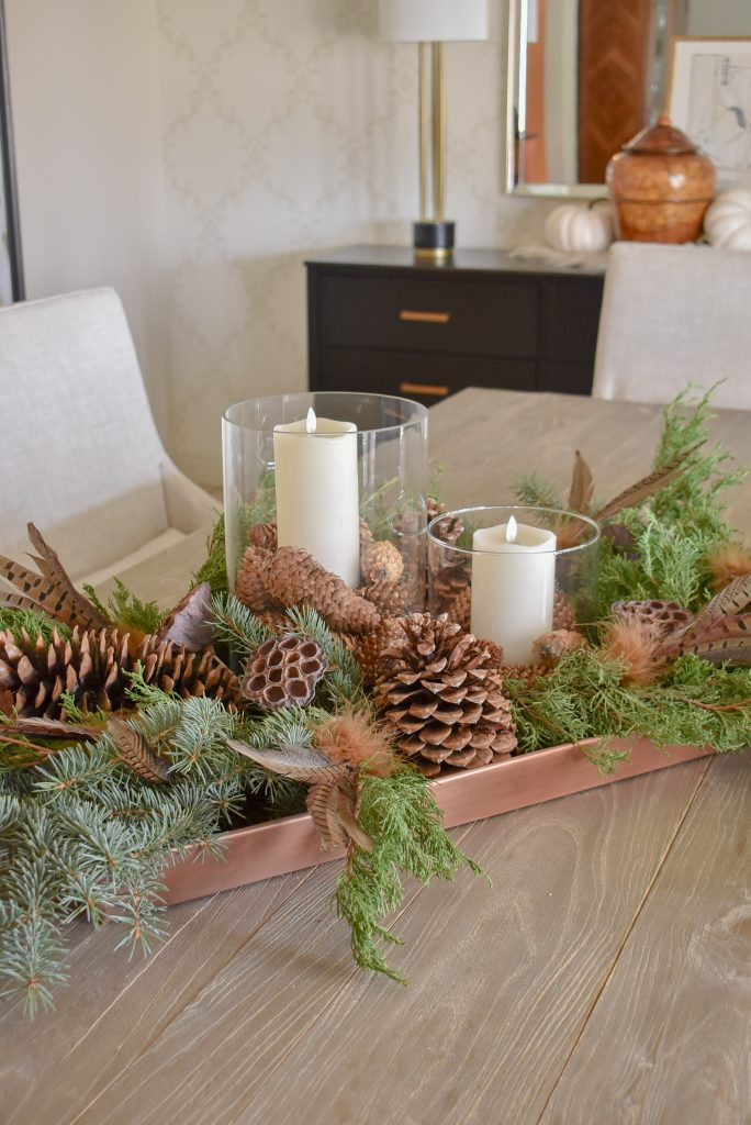 Natural greenery and pine cones on a Fall Centerpiece on a copper tray