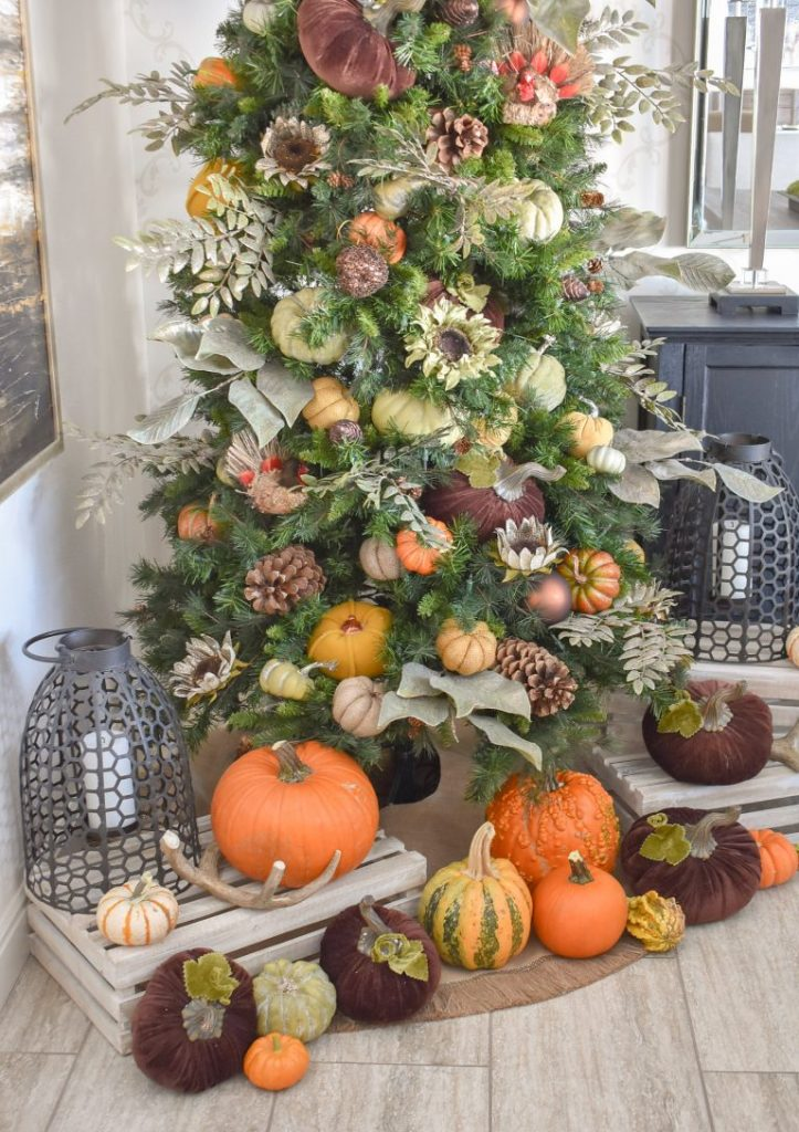 A Christmas Tree decorated for Thanksgiving with pumpkins and fall decor
