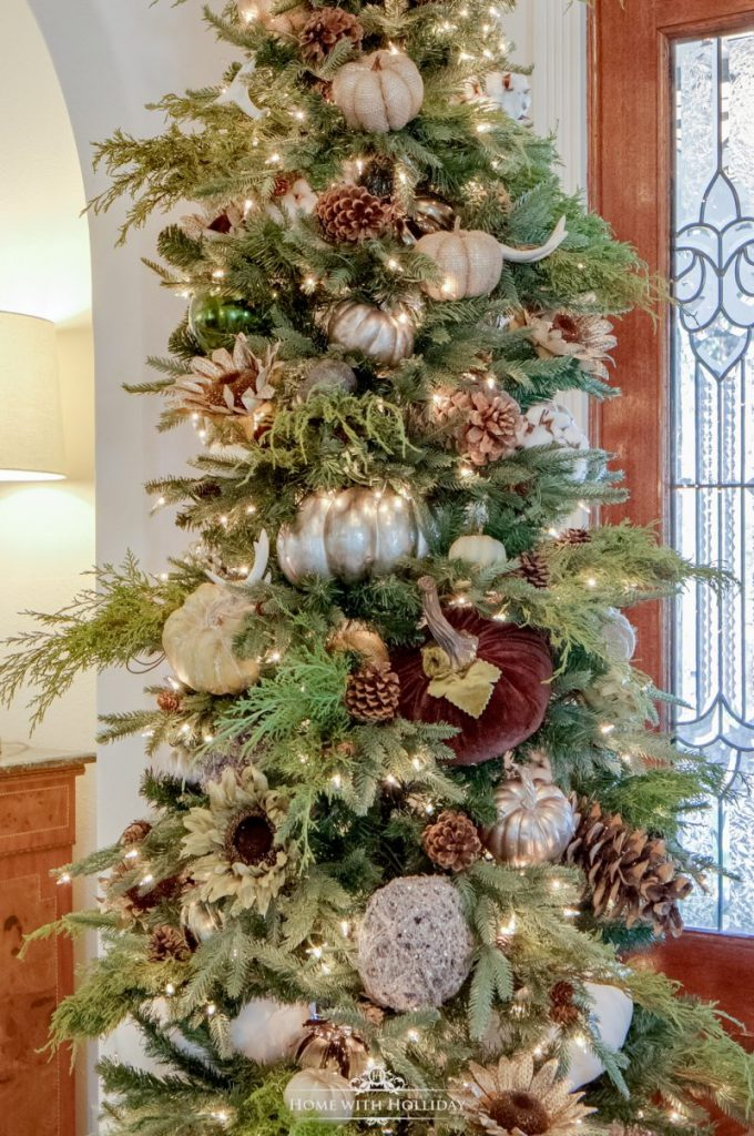 A Christmas Tree decorated for Thanksgiving with pumpkins and fall themed accents