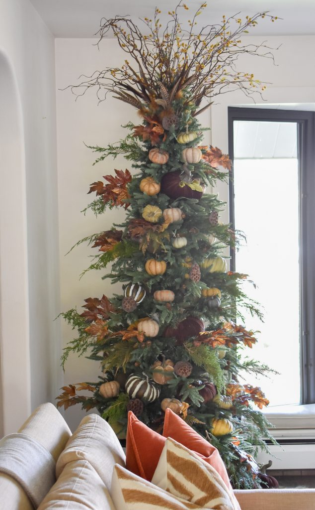A Christmas Tree decorated with fall decor for Thanksgiving