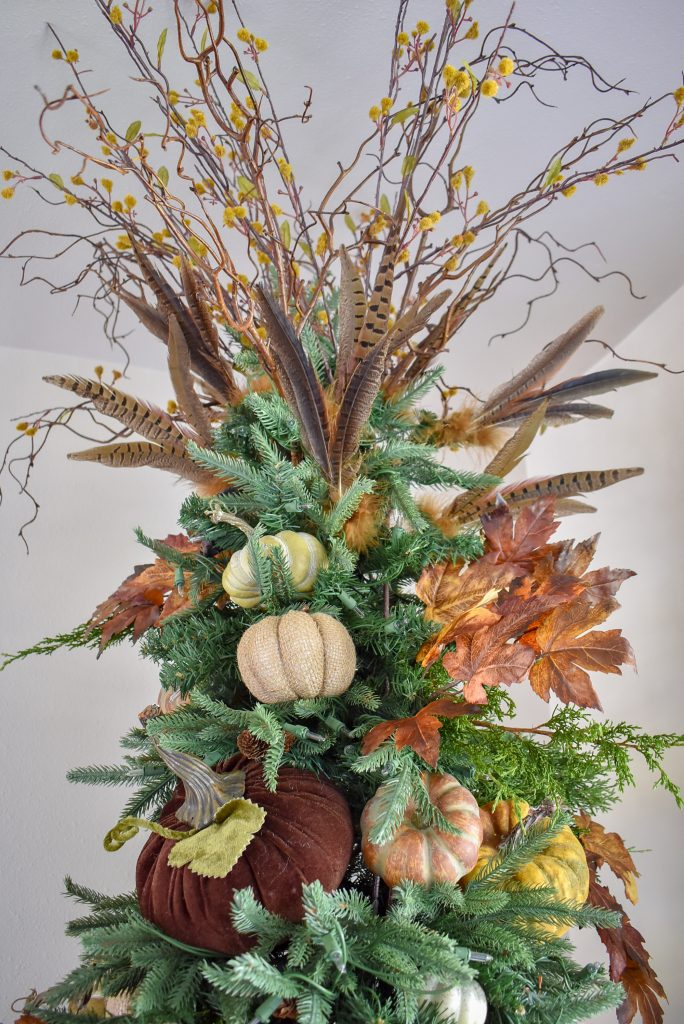 The topper on a Christmas Tree decorated for Thanksgiving or Fall with branches and feathers