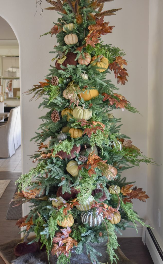 A Christmas Tree decorated with pumpkins and fall decor for Thanksgiving