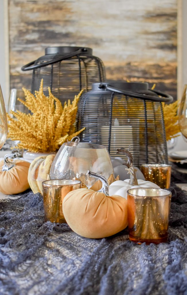 Black, Harvest Gold, and White Centerpiece on a Moody Fall Tablescape on a marble table