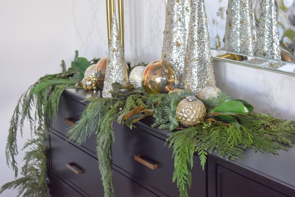 A Christmas Cone Tree Centerpiece with Evergreens and Gold on a black buffet