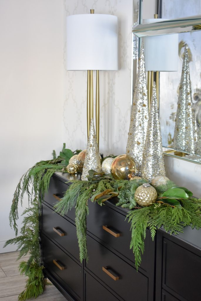 A Christmas Cone Tree Centerpiece with Evergreens and gold Christmas Ornaments on a black buffer