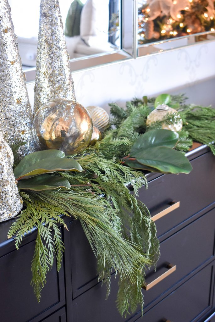 A Christmas Cone Tree Centerpiece with Evergreens on a black buffet