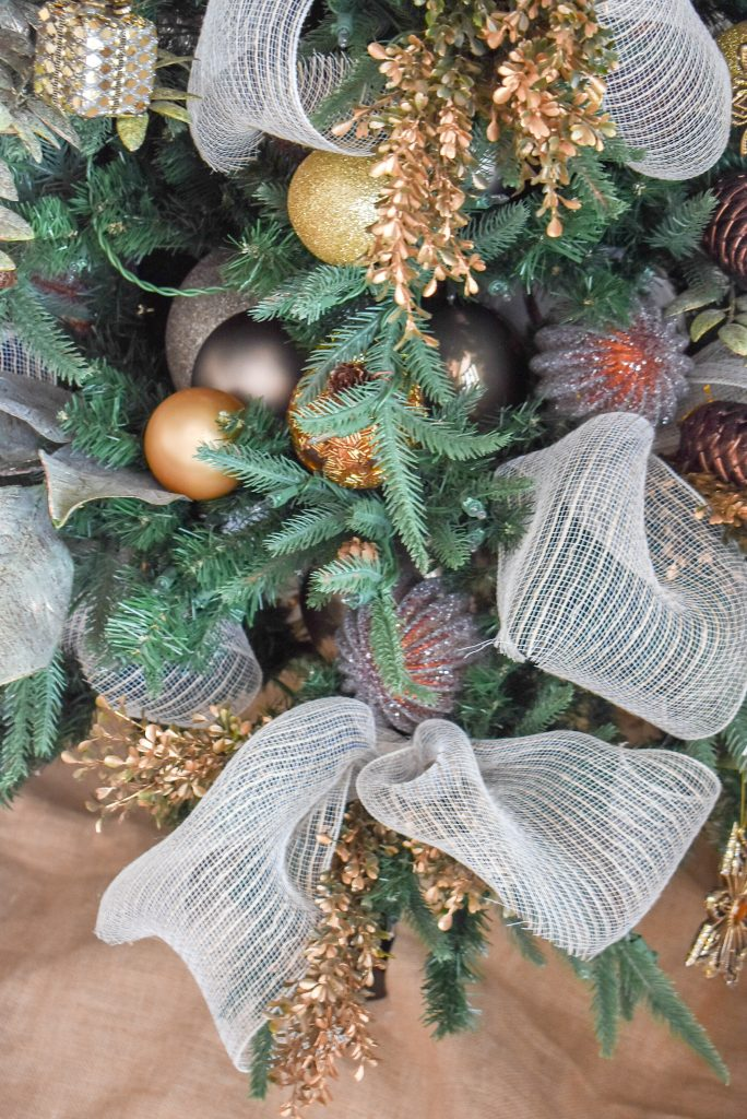 A close-up of a Christmas Tree in a Green and Gold Fresh Evergreen Christmas Home Tour