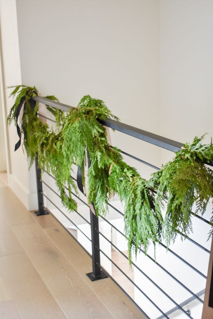 A stair railing decorated with fresh evergreens for Christmas
