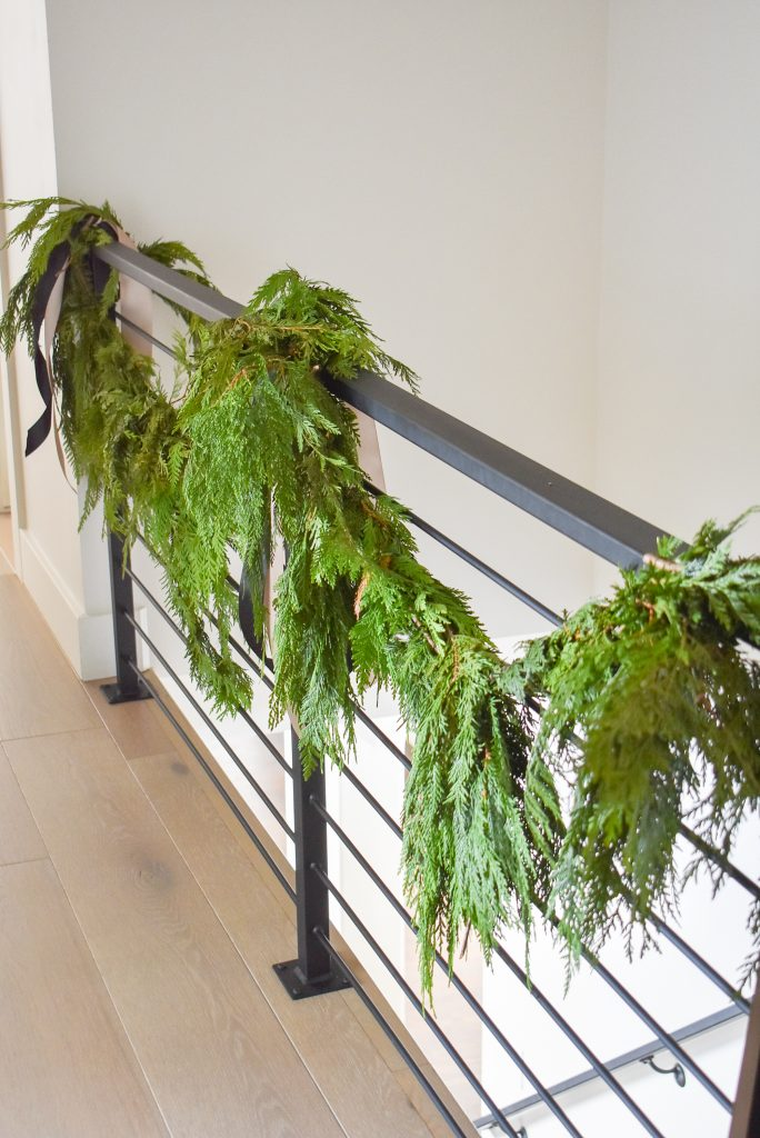 A simple stair railing decorated for Christmas with Fresh Evergreens