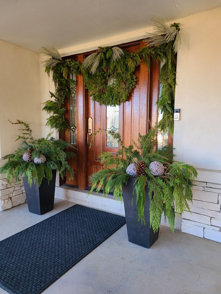 A front porch decorated for Christmas with Fresh Evergreens