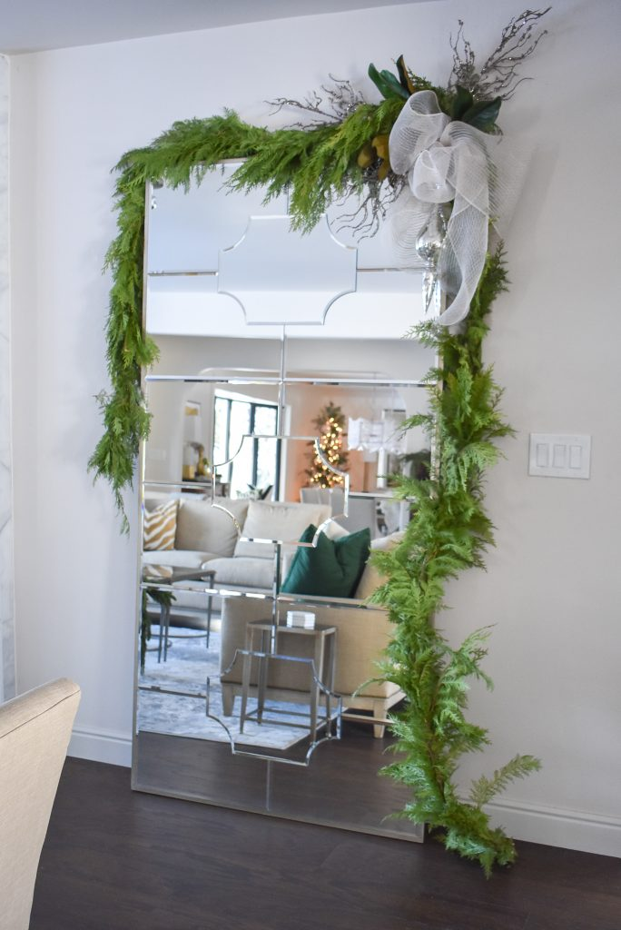 A leaner mirror decorated for Christmas with Fresh Evergreens