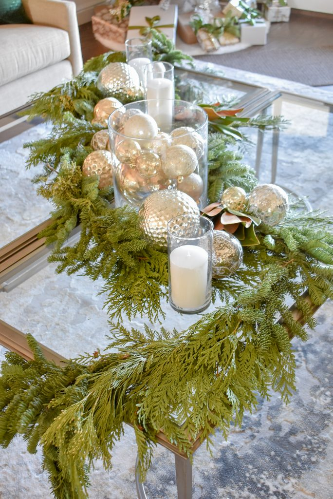 An Elegant Silver and Gold Christmas Centerpiece with Evergreens draping off the coffee table