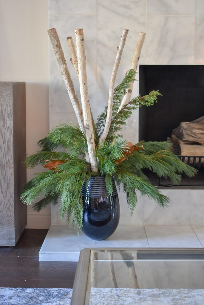 An Christmas Arrangement with birch logs and natural evergreens on a fireplace