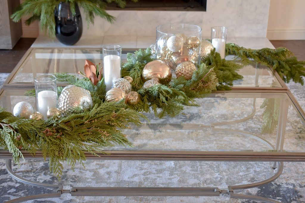 A Silver and Gold Christmas Centerpiece with Evergreens on coffee tables