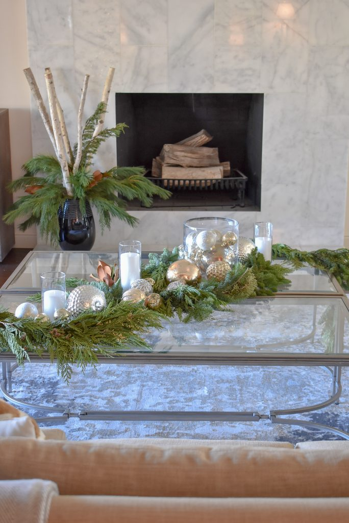 A Silver and Gold Christmas Centerpiece with Evergreens in front of a marble fireplace