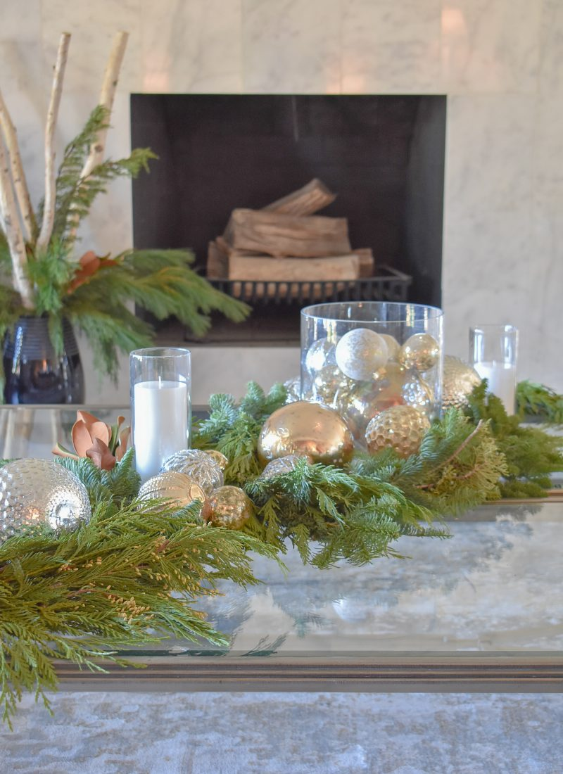 A Silver and Gold Christmas Centerpiece with Evergreens on glass coffee tables