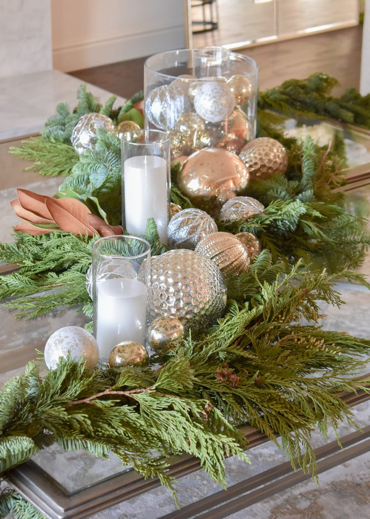 Silver and Gold Christmas Centerpiece with Evergreens on a glass coffee table