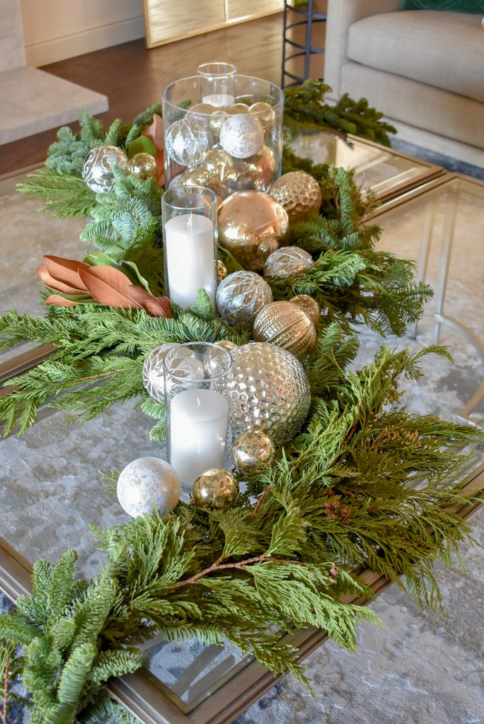 An Elegant Silver and Gold Christmas Centerpiece with Evergreens on glass coffee table