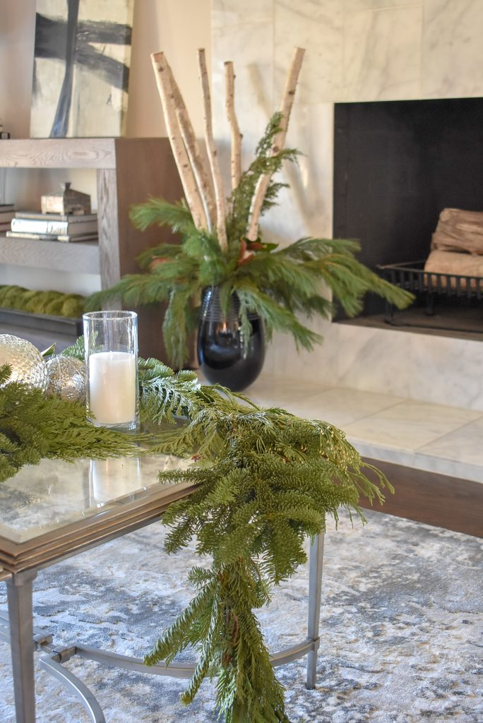 A Silver and Gold Christmas Centerpiece with Evergreens in a living room
