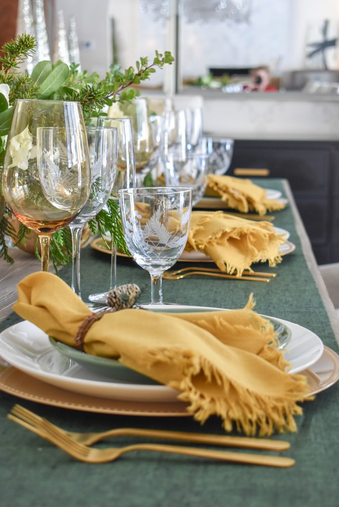 An Evergreen and Gold Christmas Table Setting with gold napkins