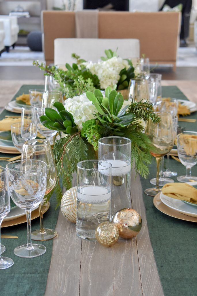 An Evergreen and Gold Christmas Table Setting in a dining room