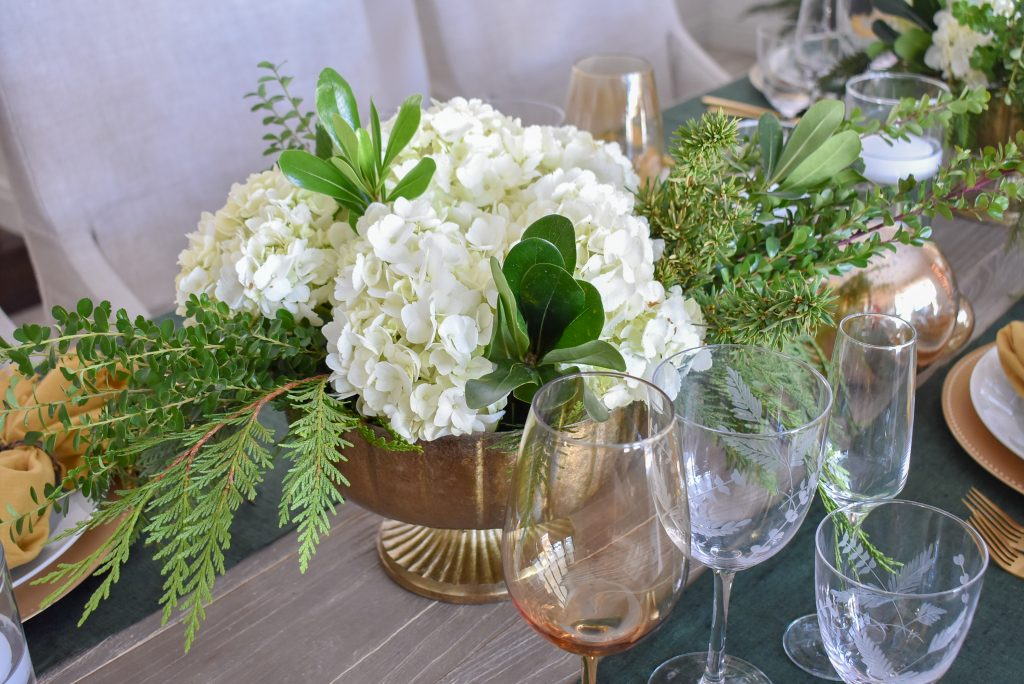 Centerpiece on an Evergreen and Gold Christmas Table Setting with Hydrangeas