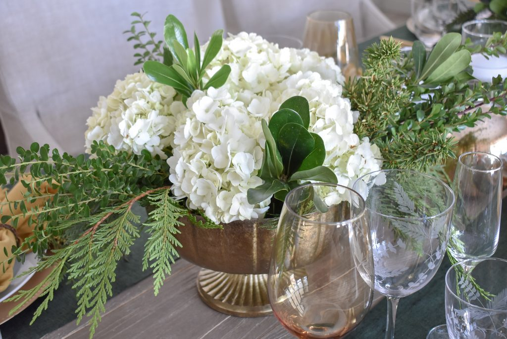 Centerpieces on Evergreen and Gold Christmas Table Settings