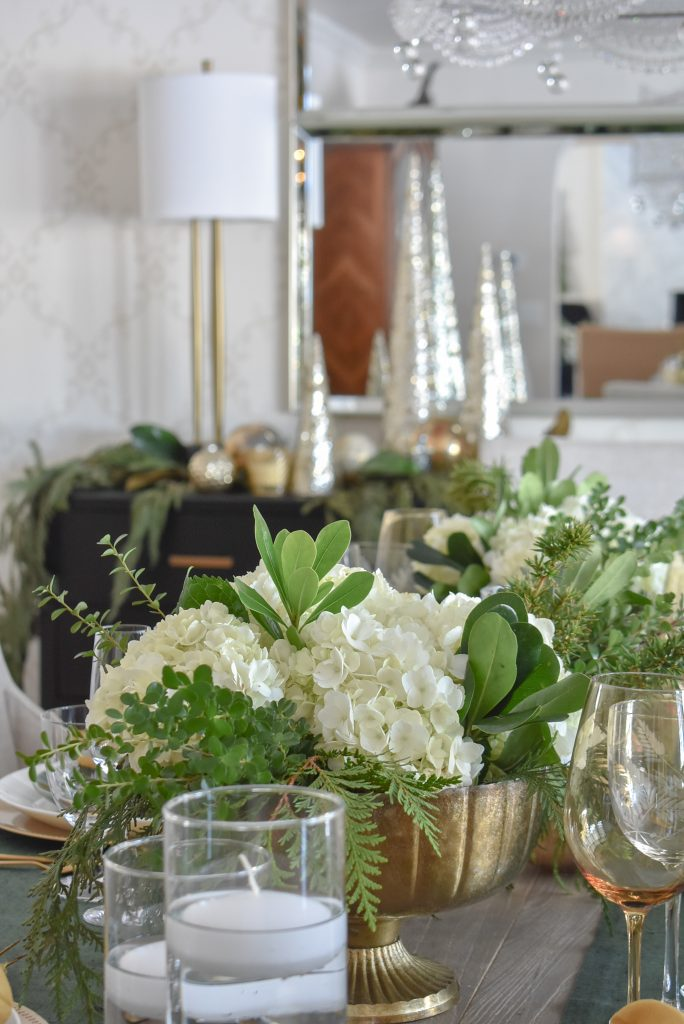 A Centerpiece on an Evergreen and Gold Christmas Table Setting