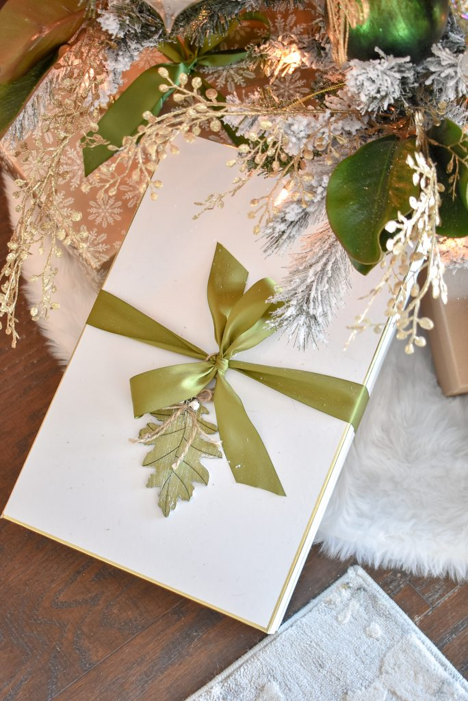 A gift wrapped below a Green and Gold Flocked Christmas Tree