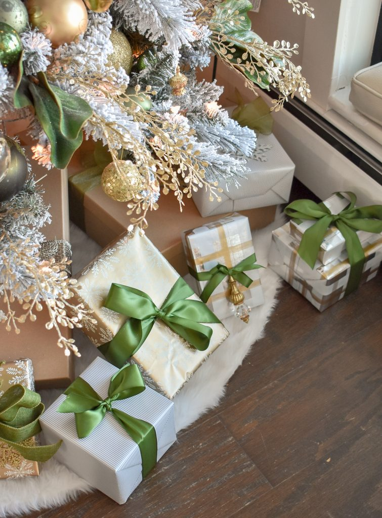 Gifts wrapped under a Green and Gold Flocked Christmas Tree