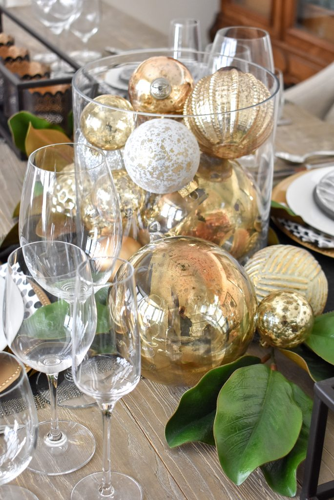 A Christmas ornament centerpiece on a Modern Glam Table Setting with Black and Gold and Silver