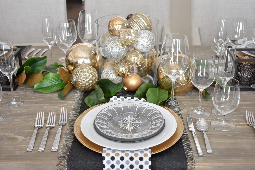 The place settings on a Modern Glam Table Setting with Black and Gold and Silver